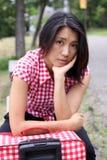 Muchacha china triste que espera con la maleta al aire libre Imágenes de archivo libres de regalías