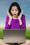 Muchacha chocada con el ordenador portátil en el campo Fotos de archivo