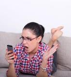 Muchacha chocada con el teléfono móvil en el sofá Fotos de archivo libres de regalías