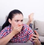 Muchacha chocada con el teléfono móvil en el sofá Imagen de archivo