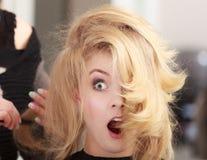 Muchacha chocada divertida con el pelo ondulado rubio del peluquero en salón de belleza Fotografía de archivo