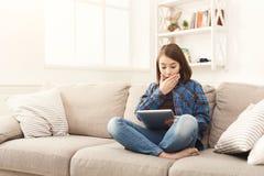 Muchacha chocada jóvenes con la tableta digital en casa Foto de archivo libre de regalías