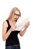 Muchacha chocada que lee la revista para mujer Imagenes de archivo