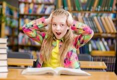 Muchacha chocada que lee un libro en la biblioteca Fotografía de archivo