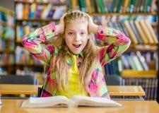 Muchacha chocada que lee un libro en la biblioteca Fotos de archivo
