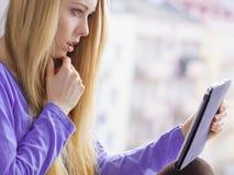 Muchacha chocada que mira en la tableta Foto de archivo libre de regalías