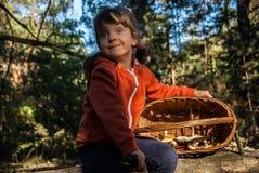 Muchacha cinco-año-vieja linda que se sienta en un árbol caido en bosque con las setas en cesta imagen de archivo libre de regalías