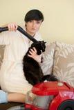 La mujer limpia el gato con el limpiador del vacum Fotos de archivo libres de regalías