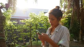 Muchacha competida con mezclada asiática joven que usa el teléfono elegante para la conversación en línea del texto en el café ta metrajes