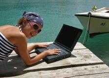 Muchacha, computadora portátil y barco bonitos en el mar Fotos de archivo