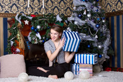 Muchacha con actual cercano el árbol de navidad Imágenes de archivo libres de regalías