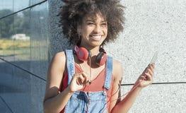 Muchacha con afro usando el teléfono móvil Foto de archivo