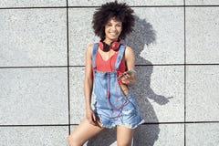 Muchacha con afro usando el teléfono móvil Imágenes de archivo libres de regalías