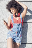 Muchacha con afro usando el teléfono móvil Imagenes de archivo