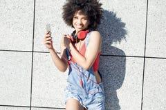 Muchacha con afro usando el teléfono móvil Fotografía de archivo libre de regalías