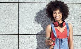 Muchacha con afro usando el teléfono móvil Fotos de archivo