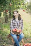 Muchacha con Apple en el manzanar Fotos de archivo
