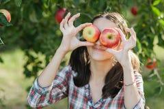 Muchacha con Apple en el manzanar Imagenes de archivo