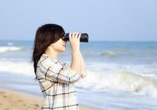 Muchacha con binocular en la playa Foto de archivo libre de regalías