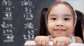 muchacha con cálculos matemáticos del dibujo de tiza sobre la pizarra Fotos de archivo