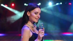 Muchacha con champán en la iluminación cercana oscura del concierto almacen de metraje de vídeo