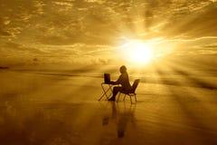 Muchacha-con-computadora-en-puesta del sol-en--playa Foto de archivo libre de regalías