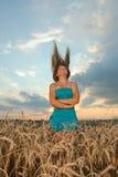 Muchacha con desgaste del estilo ocasional contra el cielo de la puesta del sol Foto de archivo