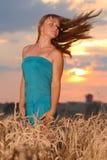 Muchacha con desgaste del estilo ocasional contra el cielo de la puesta del sol Imagen de archivo