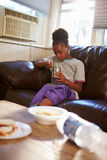 Muchacha con dieta de los pobres que come la comida en Sofa At Home Fotografía de archivo
