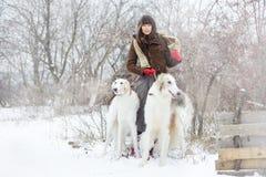 Muchacha con dos galgos en invierno, nieve que cae Fotos de archivo libres de regalías