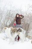 Muchacha con dos galgos en invierno, nieve que cae Foto de archivo libre de regalías
