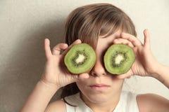Muchacha con dos pedazos de kiwi Fotografía de archivo