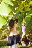 Muchacha con el árbol de plátano en trópico Fotos de archivo