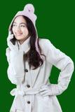 Muchacha con el abrigo de invierno que tiene una llamada de teléfono Imágenes de archivo libres de regalías