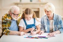 Muchacha con el abuelo y la abuela que se sientan en la tabla y que unen Fotos de archivo libres de regalías