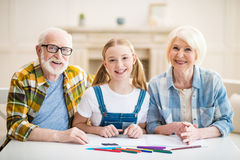 Muchacha con el abuelo y la abuela que se sientan en la tabla y que unen Imagen de archivo