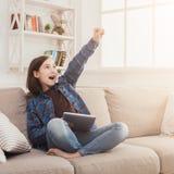 Muchacha con el artilugio en el sofá en casa Fotografía de archivo libre de regalías