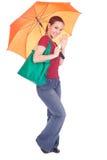 Muchacha con el bolso de compras y el paraguas anaranjado Imagen de archivo libre de regalías