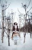Muchacha con el bolso en la nieve entre Hogweed Foto de archivo
