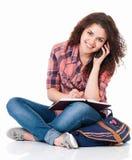 Muchacha con el bolso que se sienta en piso y que habla en el teléfono celular Fotos de archivo libres de regalías