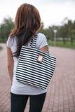 Muchacha con el bolso sobre su hombro al aire libre Fotografía de archivo