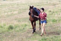 Muchacha con el caballo marrón Imagen de archivo