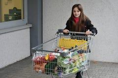 Muchacha con el carro de compras Foto de archivo