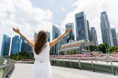 Muchacha con el centro de la ciudad aumentado de los brazos adentro de Singapur Fotografía de archivo