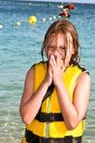 Muchacha con el chaleco de vida en la playa Imágenes de archivo libres de regalías