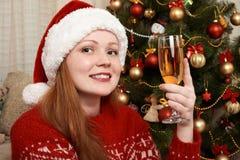 Muchacha con el champán vestido como santa en la decoración de la Navidad en casa Noche Vieja y concepto de las vacaciones de inv foto de archivo
