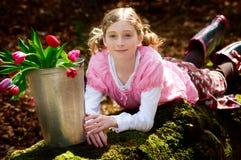 Muchacha con el compartimiento lleno de tulipanes Imagen de archivo libre de regalías