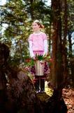 Muchacha con el compartimiento lleno de tulipanes en un bosque Fotografía de archivo libre de regalías