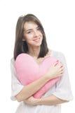 Muchacha con el corazón de la almohada del rosa de la tarjeta del día de San Valentín Foto de archivo