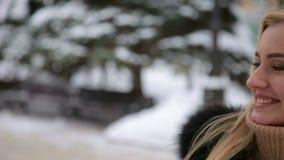Muchacha con el corazón de las manos, en paseo en parque del invierno almacen de video